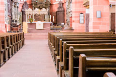 Interior of a beautiful old catholic church from below with marble floor, wooden pews, and light streaming onto altar Stock Photos