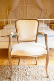 Interior of bedroom. Canopy bed and retro chair. Royalty Free Stock Images
