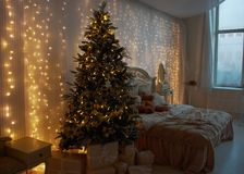 Interior of the bedroom, prepared for the New Year and decorated with a Christmas tree and gifts. Luminous garlands hang on the wa Stock Photos