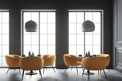 Black loft cafe interior. Interior of a black cafe corner with a concrete floor, round black tables and yellow chairs. 3d rendering mock up Royalty Free Stock Photos