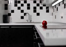 Interior of black and white kitchen with red apple Stock Images