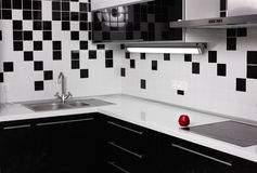 Interior of black and white kitchen with red apple Stock Photo