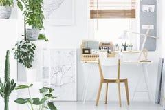 Interior blanco con las plantas, cartel, escritorio, silla de Ministerio del Interior y foto de archivo libre de regalías