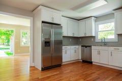 Interior blanco de la cocina con el fregadero, los gabinetes, y los suelos de parqué Foto de archivo libre de regalías