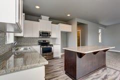 Interior bonito da sala da cozinha com armários brancos, ilha de cozinha e partes superiores contrárias do granito imagem de stock royalty free