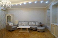 Interior bonito da sala de visitas com assoalhos de folhosa e fogo rujir da chaminé na casa luxuosa nova Fotografia de Stock Royalty Free