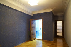 Interior bonito da sala de visitas com assoalhos de folhosa e fogo rujir da chaminé na casa luxuosa nova Fotografia de Stock