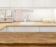 Interior borrado da cozinha com a tabela dinning de madeira na parte dianteira fotografia de stock