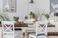 Interior branco da sala de jantar com cartazes e cadeiras na tabela de madeira com flores Foto real fotografia de stock royalty free