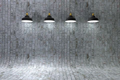 Interior brick wall illuminated by lamps above Stock Images