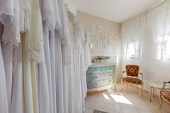 Interior of bridal salon. Beautiful wedding dress on a hangers. Royalty Free Stock Images