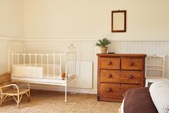 Cot in the comfortable bedroom of a country home. Interior of a bright master bedroom with a bed and baby`s cot in a contemporary residential home Royalty Free Stock Images