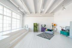 Interior brillante del estudio o de la sala de estar de la foto con la ventana grande, alto techo, piso de madera blanco, sofá mo Foto de archivo libre de regalías