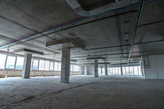Interior of the building under construction. Crude interior of the building under construction with large windows Stock Photos