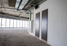 Interior of the building under construction. Crude interior of the building under construction with large windows and two metallic doors Royalty Free Stock Photography
