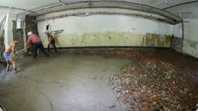 Interior of building under reconstruction. Group of men covering office floor with liquid concrete. Time lapse stock video