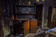 Interior of the burned by fire house, burned furniture Royalty Free Stock Photos