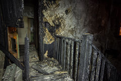 Interior of the burned by fire house, burned wooden stairs Stock Photos