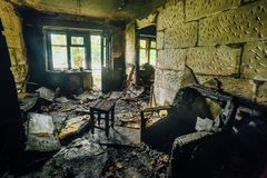 Interior of a burnt by fire apartment in an apartment building, burned furniture Royalty Free Stock Image