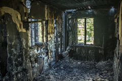 Interior of a burnt by fire apartment in an apartment building. Burned wooden walls.  Stock Photography