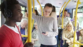 Interior Of Bus With Passengers. Interior of crowded bus with passengers listening to music and using mobile phone.Shot on Sony FS700 in PAL format at a frame stock video footage