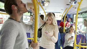 Interior Of Bus With Passengers. Interior of crowded bus with passengers listening to music and using mobile phone.Shot on Sony FS700 in PAL format at a frame stock video