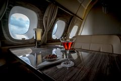 Interior of a business class of a commercial passenger plane. An armchair and a window, a table and a cocktail glass with a drink and almonds. Focus on a glass stock photos
