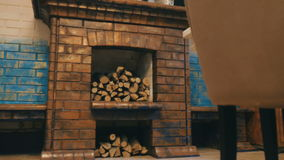 The interior of a cafe with a fireplace and firewood. A brick fireplace stands by the wall in a restaurant. Firewood is filled in. The camera approaches to the stock video footage
