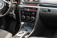 The interior of the car Mazda 3 with a view of the steering wheel, dashboard, seats and multimedia system with light gray trim and stock image