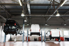 Interior of car repair station,cars on maintenance. Interior of car repair station, cars on maintenance lifted up on elevators Stock Photography