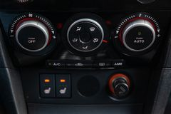 The interior of the car with a view of the dashboard, front seat heater buttons and climate-controle with light gray trim. Novosibirsk, Russia - 04.12.2019: The royalty free stock photography