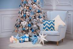 Interior casero de la Navidad - una butaca acogedora y un abeto adornado en colores blancos azules Fotos de archivo libres de regalías