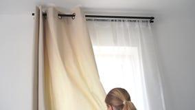 Interior casero una mujer rubia de las cortinas europeas del aspecto una ventana en el dormitorio almacen de metraje de vídeo