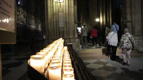 Interior of the cathedral of Notre Dame de Paris with multiple candles and tourists. Paris, France - Circa 2017: Group of international tourists walking near the stock video footage