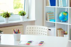 Interior of child room with white table and colorful pencils on. Him and shelf with books on background stock photo