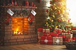 Interior christmas. magic glowing tree, fireplace, gifts royalty free stock images