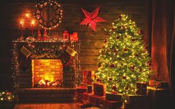 Interior christmas. magic glowing tree, fireplace gifts in dark royalty free stock image