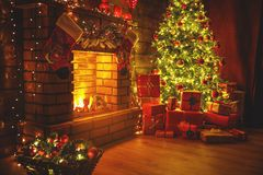 Interior christmas. Magic glowing tree, fireplace gifts in dark royalty free stock photos
