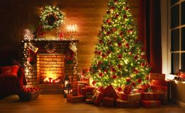 Interior christmas. magic glowing tree, fireplace, gifts in  dark. At night