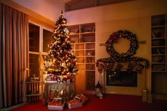 interior christmas. magic glowing tree, fireplace gifts in dark at night stock image