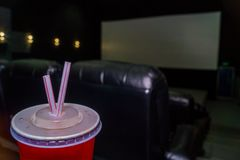 The interior of a cinema hall with black leather seats and a white screen. The film does not show and no people. The interior of a modern cinema hall for stock photo
