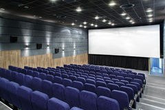 Interior cinema hall with plenty of seating and a big screen Royalty Free Stock Images
