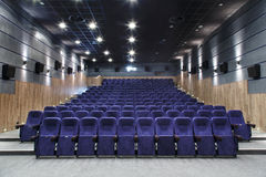 Interior cinema hall with plenty of seating and a projector Stock Photos