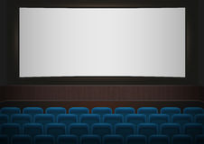 Interior of a cinema movie theatre. Blue cinema or theater seats in front of white blank screen. Empty Cinema auditorium Royalty Free Stock Image