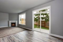 Interior cinzento da sala de visitas Windows e portas de vidro que negligenciam o pátio traseiro imagem de stock