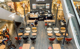 Interior of city cafe inside the moderm shopping mall with customers. VIENNA, AUSTRIA - JUN 6, 2013: Interior of city cafe inside the moderm shopping mall with Royalty Free Stock Photos