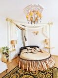 Interior clásico de oro del dormitorio con la cama redonda Foto de archivo libre de regalías