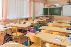 Interior class in elementary school, students desks and desk teachers board in the background Stock Photos
