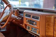 Interior of a classic vintage car. With a brown dashboard and steering wheel with wood trim and column controls Stock Photo
