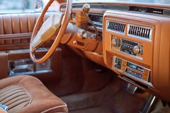 Interior of a classic vintage car. With column steering and wood trim on the dashboard viewed through the passenger window Royalty Free Stock Image